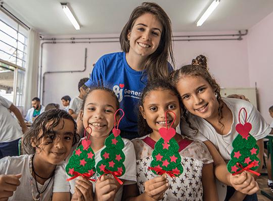 A voluntária Bianca Oliveira participou com as crianças da atividade de fazer enfeites em forma de árvore de Natal.