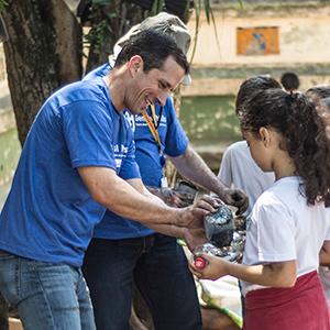 Presidente da Gmills, Ricardo Fernandez, ajudou crianças a criar horta vertical.